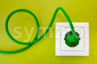 Green power plug into white power socket Stock Photo