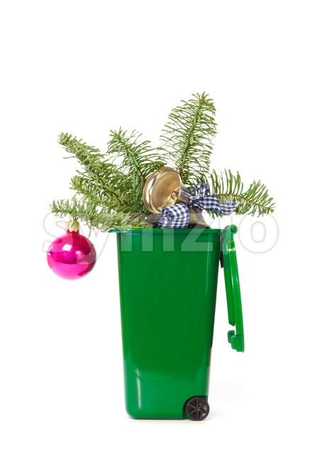 Christmas decorations in the green wheelie bin against white background