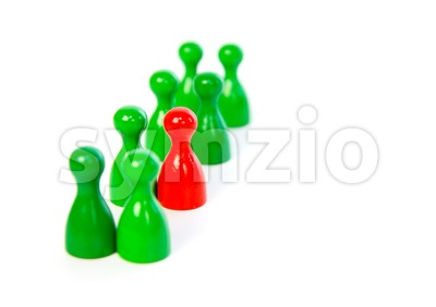 Red pawn in a line-up of green pawns Stock Photo