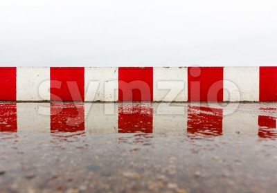Red white concrete wall on the asphalt Stock Photo
