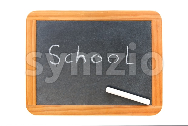 School written on vintage chalkboard and a chalk on the board, isolated on white