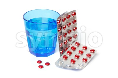 Pill strips and a blue glass with water Stock Photo