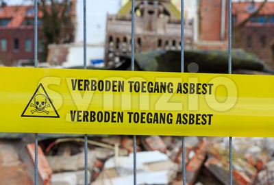 Yellow tape on fence with Dutch text 'no trespassing asbestos' Stock Photo