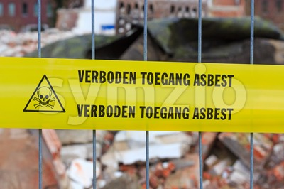 Yellow tape on fence with Dutch text 'no entry asbestos' Stock Photo