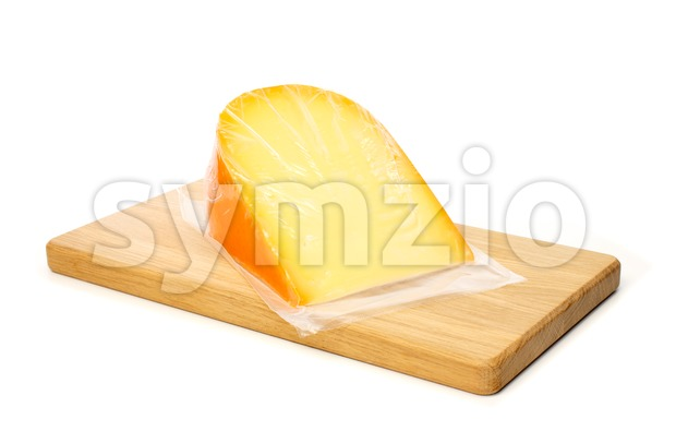 Cheese in vacuum packing on cutting board Stock Photo