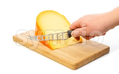 Hand cuts with knife the cheese on a cutting board Stock Photo