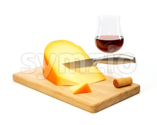 Knife in yellow cheese on a cutting board with a glass of red wine Stock Photo