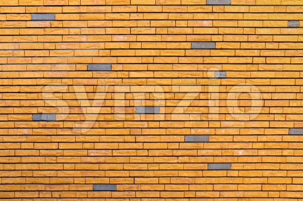 Yellow brick wall with  irregular surface interspersed with some gray bricks