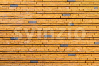 Yellow brick wall interspersed with some gray bricks Stock Photo
