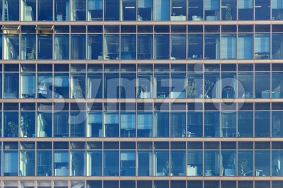 Glimpse into the workplaces of an office building with blue glass windows Stock Photo
