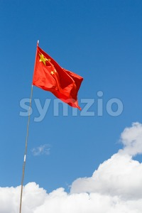 Waving Chinese flag against blue sky Stock Photo