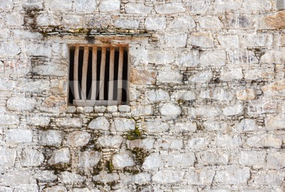 Prison cell window with wooden bars in a white brick wall Stock Photo