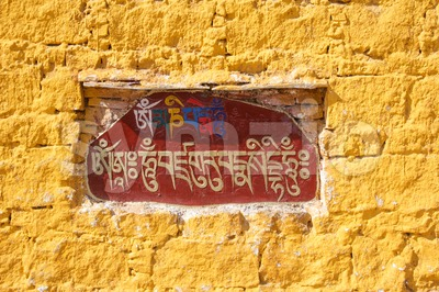 The Sanskrit mantra 'Om mani padme hum' inscribed and painted on a mani stone embedded in a wall of the Potala Palace in Lhasa Stock Photo