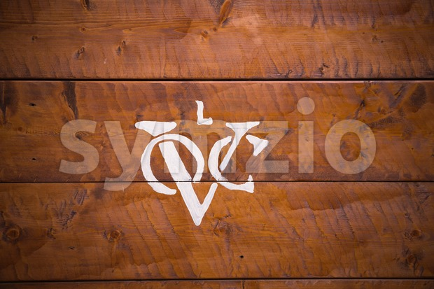 Logo of the Dutch United East India Company (Vereenigde Oostindische Compagnie) on background of wooden planks.  It is often ...