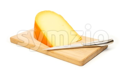 Yellow cheese and kitchen knife on a cutting board Stock Photo