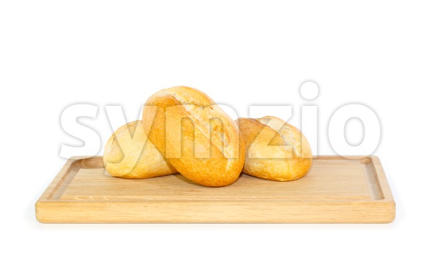 Fresh German bread rolls on a wooden breakfast tray against white background