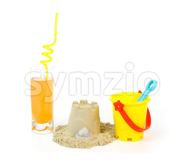 Yellow toy bucket, sandcastle with shell and a refreshing drink against white background