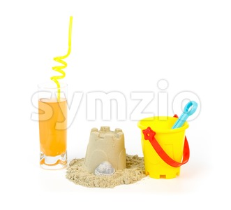 Toy bucket, sandcastle and a refreshing drink Stock Photo