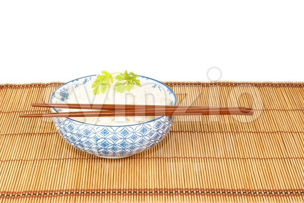 Bowl of rice with chopsticks against white backgrond Stock Photo