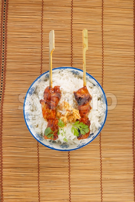 View from above on a bowl of rice with pork satay Stock Photo