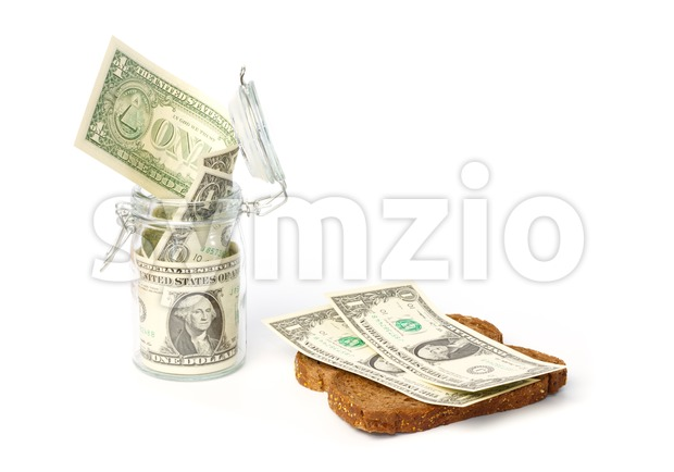 Dollars in a jar and on a slice of bread Stock Photo