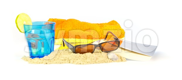Holiday on the beach with towels, sunglasses, a book and a drink Stock Photo