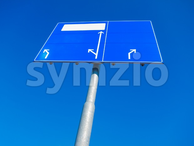 Blank blue direction sign pointing in different directions against blue sky