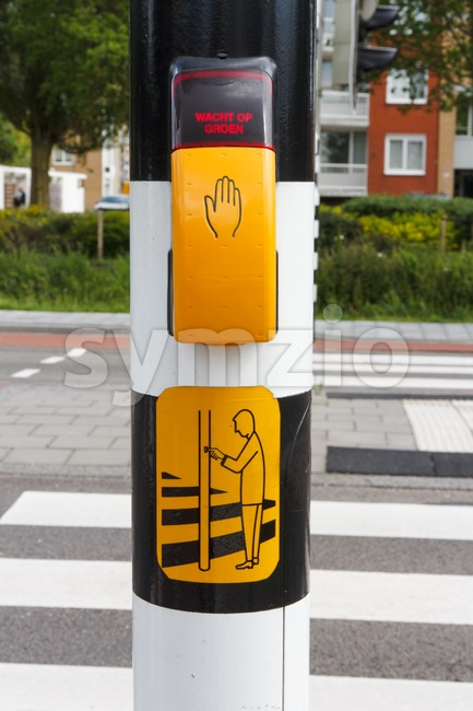 Dutch pedestrian light with button and text  to wait for green light Stock Photo