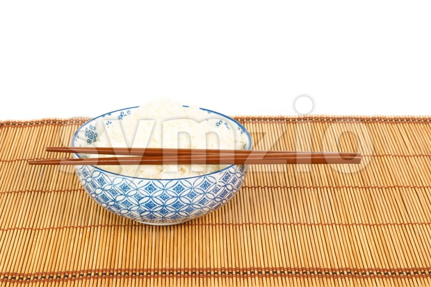Bowl of rice with chopsticks and table mat against white backgrond Stock Photo