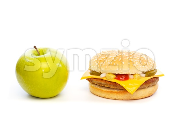 Choose: green apple or a cheeseburger. Against white background