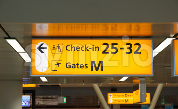 Yellow illuminated sign with gate number and check-in desks