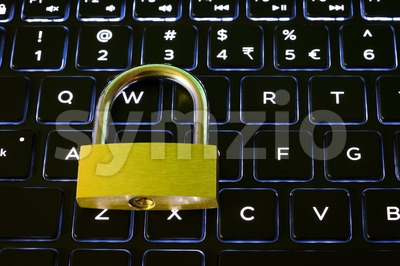 Closed security lock on backlit computer keyboard Stock Photo