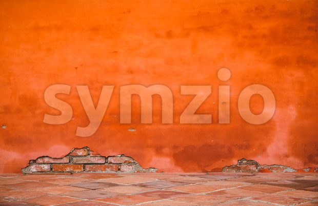 Oriental orange-red brick wall with some broken plaster