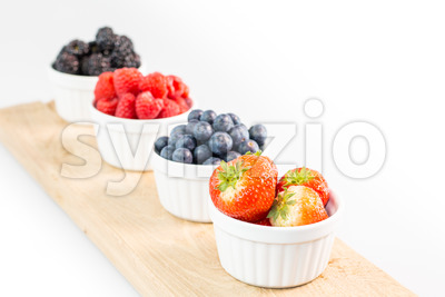 Strawberries, blueberries, raspberries and blackberries on a cutting board Stock Photo