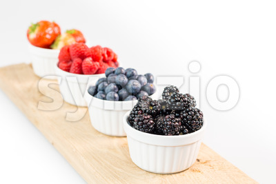 Blackberries, blueberries, raspberries and strawberries on a cutting board Stock Photo
