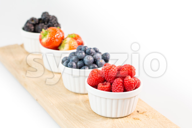 Raspberries, blueberries, strawberries and blackberries on a cutting board Stock Photo