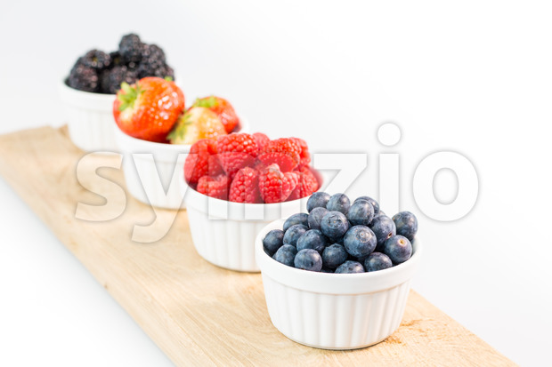 Blueberries, raspberries, strawberries and blackberries on wooden cutting board with shallow depth of field