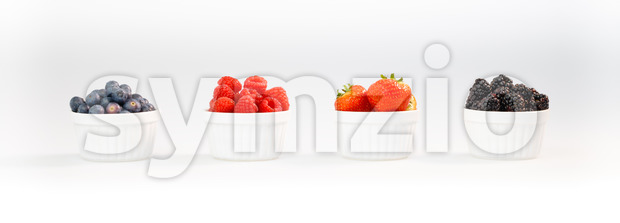 Blueberries, raspberries, strawberries and blackberries in a row Stock Photo